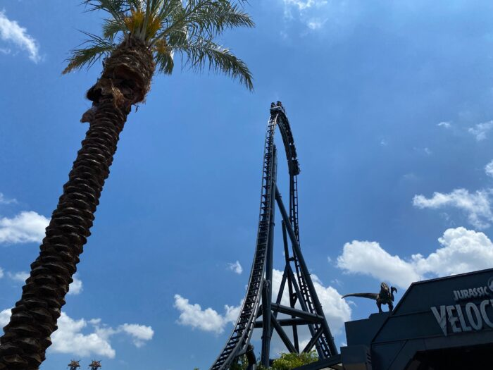 """Blue sky, a few white clouds, with palm tree in foreground and ride entrance partially visible with a dinosaur on the roof, emphasizes the height of the """"top hat"""" portion of VelociCoaster roller coaster."""