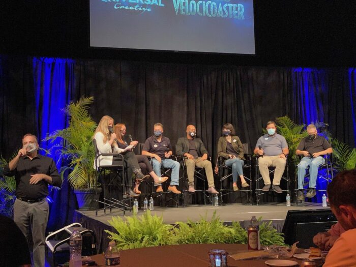 A panel of six people (white woman with red hair, white man, black man, white woman with dark hair, two white men) are seated on a dais in front of black curtained backdrop and blue lights, and tropical plants on each side and in front. To the left is a standing sign language interpreter (male, white).  Seated moderator (blonde white woman in white cardigan), poses a question to the panel.