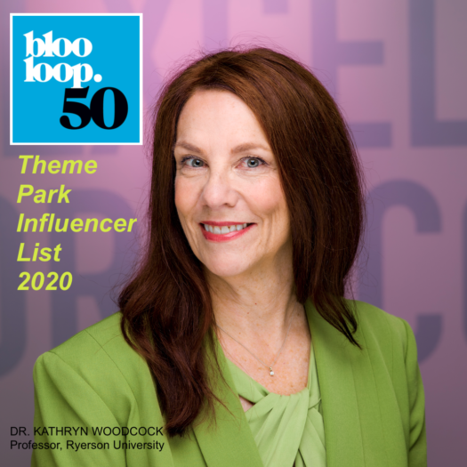 head and shoulders portrait of Dr. Woodcock (white woman with auburn hair, wearing apple green top and jacket against two-tone mauve backdrop) superimposed with logo of Blooloop 50 Theme Park Influencer list
