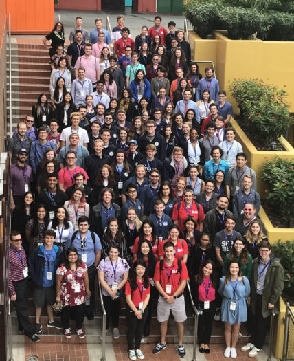 a diverse group of about 120 students at RITDC 2019 pose standing on a staircase at Universal CityWalk for a group photo, taken from a balcony